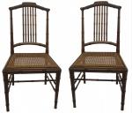Par de cadeiras em  madeira entalhada imitando cana da India, assentos em palhinha. Acompanham almofadas .NO ESTADO. Medidas 85 x 50 x 48 cm.