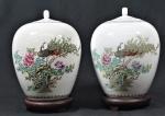 Par de vasos com tampa em porcelana oriental, decorado com faisão e flores, acompanha peanha de madeira, marca na base, selo vermelho. Alturas 30 cm.