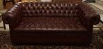 Sofá Chesterfield em couro  capitonê e pés de bolacha. Medidas 77 x 190 x 90 cm.