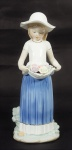 Estatueta de porcelana policromada representando Menina com cesta de flores. Alt. 30 cm.