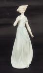 Estatueta de porcelana policromada representando Dama com passarinho . Alt 28 cm