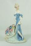 Grupo escultórico de porcelana policromada representando Dama com carrinho de flores. Alt. 35 cm.