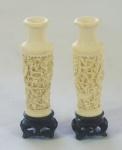 Par de pequenas ânforas em marfim esculpido, acompanha peanha em madeira, altura 11 cm (falha na borda)