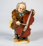 Grupo escultórico em porcelana policromada rep. Músico com violoncelo(braço do instrumento quebrado). Alt. 13 cm
