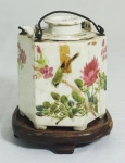 Bule para chá em porcelana chinesa policromada com inscrições com recipiente para banho Maria. Assinado na base. Medidas: 13x10x11. Acompanha base em madeira.