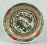 Bowl fundo em porcelana chinesa policromada decorada com dragões ao centro, acompanha peanha de madeira. Medida: 7cm de altura e 33cm de diâmetro. Apresenta pequenos bicados na borda.
