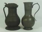 Duas jarras em estanho, uma com tampa medindo 22cm de altura e a outra sem tampa medindo 23cm de altura e com contraste na base.