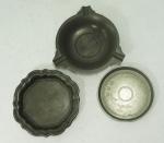 Lote composto por três peças em estanho: cinzeiro contrastado John Somers - MG, pequena salva contrastada London H.C.O. e pequena salva contrastada JS x MG com borda amassada. Medidas: 15, 14,5 e 12cm de diâmetro.