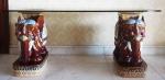 Mesa com tampo de vidro, par de elefantes em porcelana chinesa policromada na base, medindo 59x138x51cm.