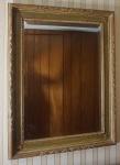 Espelho bisotado com moldura em madeira entalhada. Medida total: 90x70cm.