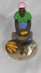 """JOÃO ALVES. """"Mulher sentada debulhando milho"""", Taiobeiras-MG, peça medindo 17 cm de altura e 12cm de diâmetro na base. Assinada na base."""