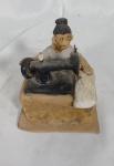 """ADALTON. """"Mulher costurando"""", Niteroi-RJ, cerâmica policromada medindo 11 x 10 x 9 cm. Assinada na lateral """"Dalton RJ 85"""". Falta dedo da mão direita."""