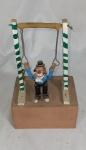 """ADALTON. """"Palhaço do circo"""", peça em cerâmica policromada e madeira medindo 22 x 13 x 9 cm. O palhaço é articulado."""
