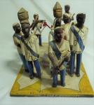 """""""Congada"""", grupo escultórico em madeira policromada com 12 figuras unidas por base plana, medindo 23 x 25 x 39 cm. Apresenta restauro e duas peças soltas."""