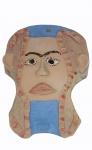 Máscara em cerâmica policromada medindo 27 x 20 cm, com orifício para ser pendurada. Assinada. Apresenta restauros.