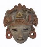 Máscara peruana em cerâmica policromada medindo 20 x 18 cm. Apresenta quebrado na testa e olho esquerdo.