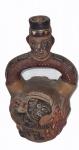 Moringa em cerâmica com figuras em relevo com policromia, medindo 23 x 13 cm.