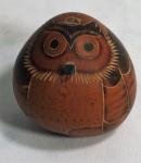 """Cabaça esculpida mo formato de coruja, com etiqueta """"Arkana"""", medindo 8 cm de altura."""