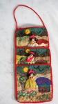 Porta coisas em tecido bordado com figuras peruanas, medindo 30 cm de altura. No estado, apresenta marcas do tempo.