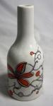 Garrafa em porcelana branca com decoração floral da perfumaria Phebo, medindo 22 cm de altura e 9,5 cm de diâmetro.