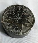 Porta joias em pedra sabão cinza com tampa decorada, medindo 3 cm de altura e 6,5 cm de diâmetro.