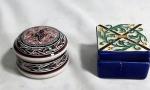 Souvenirs de Portugal: dois (2) porta joias em porcelana policromada. Um quadrado medindo 4 x 6,5 x 6,5 cm (restaurado) e outro redondo medindo 4,5 cm de altura e 7 cm de diâmetro.