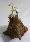 Tronco em madeira encimado por ave alimentando dois (2) filhotes no ninho, medindo 21 x 19 x 17 cm.