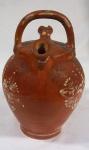 Moringa em cerâmica com alça, decorada com flores e folhas, medindo 22 cm de altura e 15 cm de diâmetro. Alça apresenta restauro e bicado.