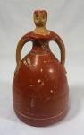 """""""Figura feminina"""", moringa (sem tampa) em cerâmica com resquícios de decoração floral, medindo 29 cm de altura e 16 cm de diâmetro. Necessita restauro."""