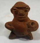 Apito em cerâmica, com figura humana estilisada, medindo 10 x 8,5 x 9 cm.