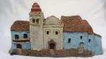 Grupo escultórico, com igreja e duas(2) casas, em cerâmica policromada, com detalhes de portas e janelas, medindo 17 x 31 x 14 cm. Apresenta rachadura na base.