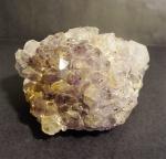 Cristal de rocha na cor violeta, com pequenos pontos pretos, medindo 7 x 11 x 12 cm.