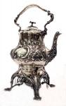 Samovar em prata inglesa contrastada, ricamente trabalhada em relevo com palmas e flores, pega no formato de flor. Alt. 43 cm. Peso aprox. 2.600 gr.
