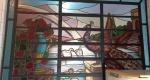 """Vitral com junções do vidro em chumbo, pinturas de vaso de flores, lago e animais no vidro queimado a fogo, """"moldura"""" (parte em vidro azul) colocada posteriormente à fabricação, para encaixe no local desejado, medindo no total 150 x 192 cm. (peça está chumbada na parede, retirada por conta do comprador)(RETIRADA RUA SANTO CRISTO)"""