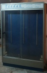 Vitrine loja de presentes Tzedaka, estrutura em madeira, alumínio e vidro, medindo 2,00x1,34x0,30 cm fundo em fórmica azul, suportes em alumínio para fixação de mãos francesas (não acompanham) para prateleiras de vidro, luminárias partes elétrica no estado e não testado, não acompanhe lâmpadas, sem chave com placa de acrílico.