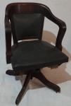 Cadeira de escritório sobre rodízios, assento e encosto em couro ecológico, base em compensado curvado, medindo 80 x 44 x 51 cm.