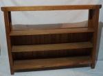 Bar/estante/livreiro apoiado em 4 pés, com 3 prateleiras em madeira clara, medindo 111 x 29 x 150 cm.