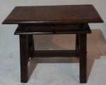 Mesa de apresentação com travessa central, apoiada em 4 pés, com 1 gaveta com puxador em madeira, medindo 54 x 74 x 41 cm.