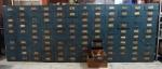 Escaninhos em madeira pintada na cor azul, gavetas com puxadores em metal (total de 120 gavetas), medindo 124 x 325 x 40 cm. No estado.